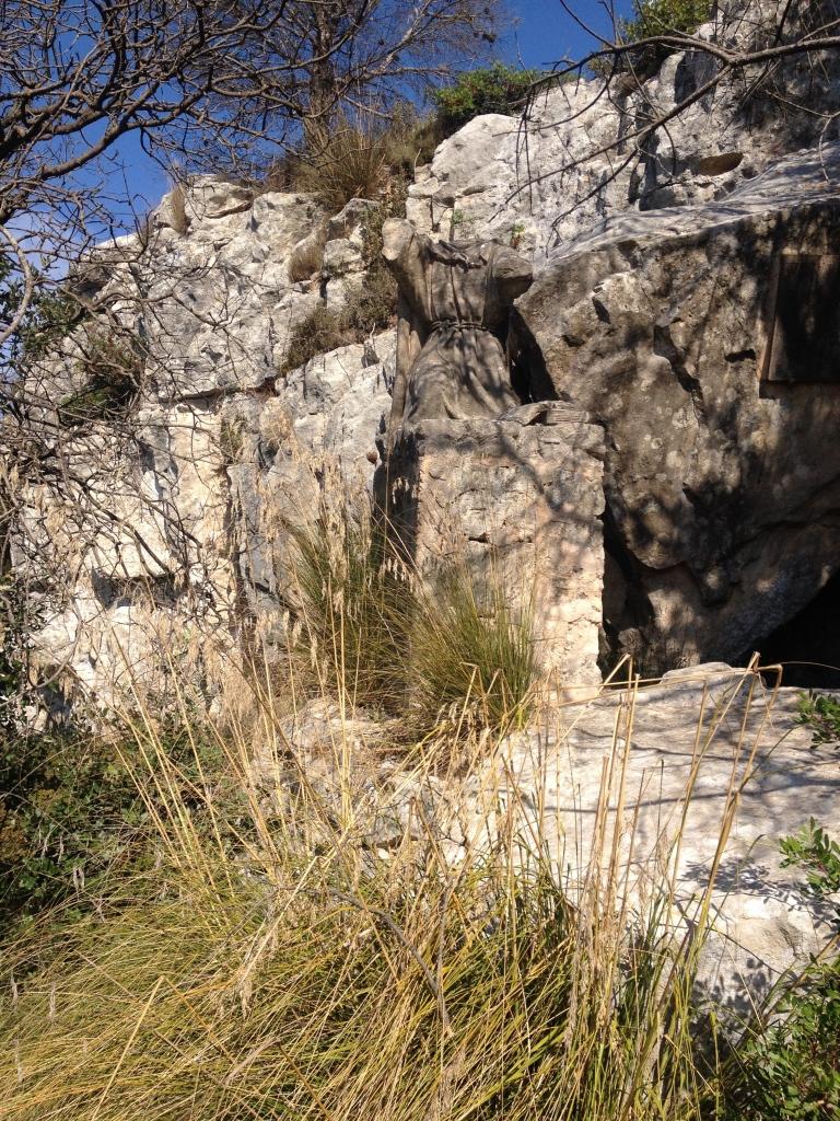 Die teilweise zerstörte Statue auf ihrem Sockel neben der Felsspalte